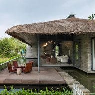 AM House is a Vietnamese holiday home surrounded by a pond and tropical gardens