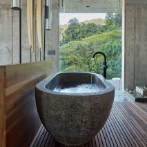 The bathroom has a a stone freestanding bath tub