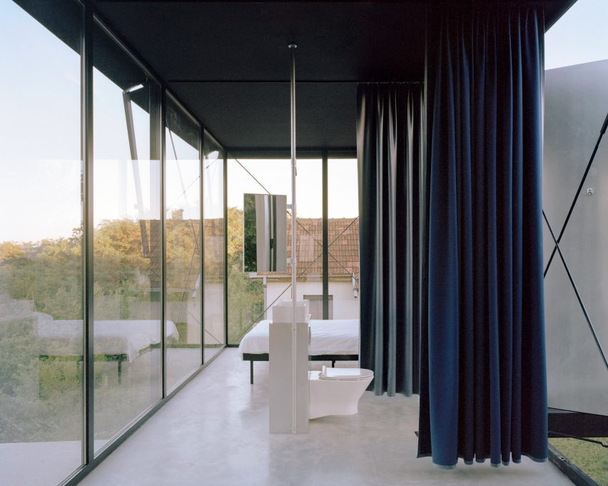 A glass-walled bedroom and bathroom