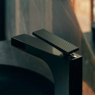 A black tap with a lever handle by Axor