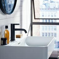 A white sink with a black tap