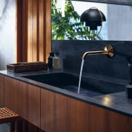 A black sink with a gold tap