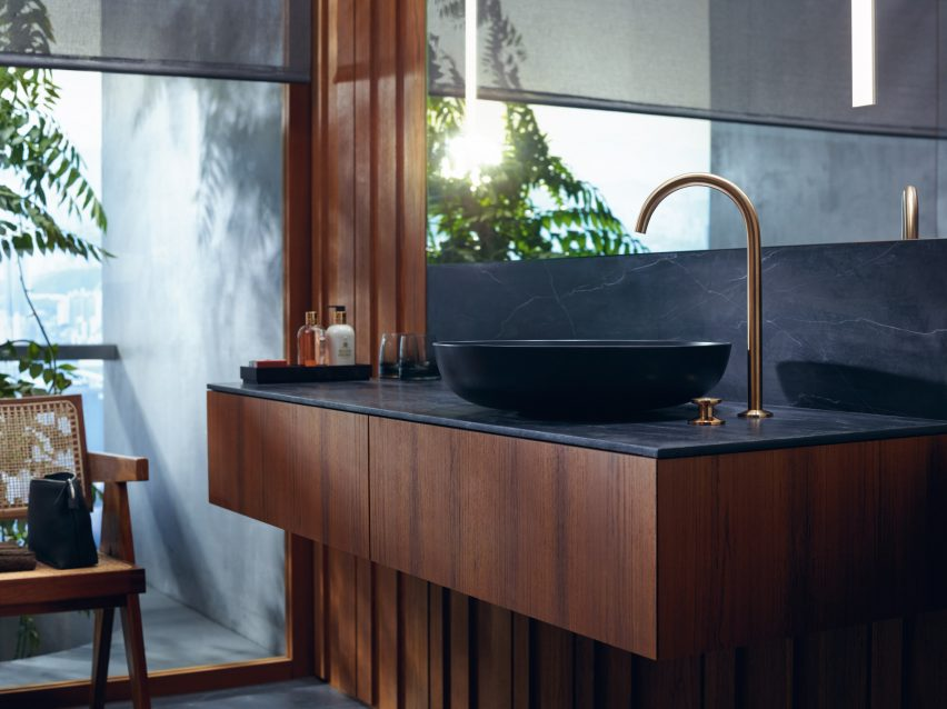 A wooden sink unit with a gold tap