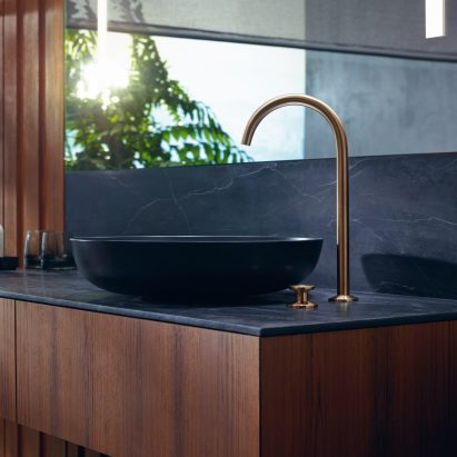 A black sink with a curved gold tap