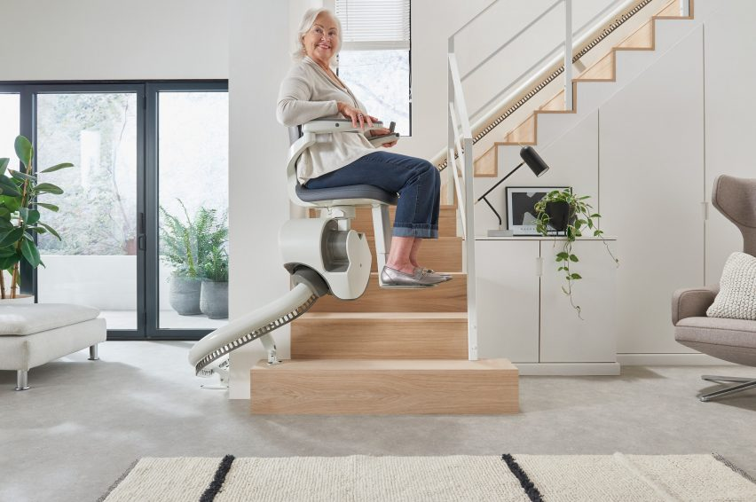 Woman riding Flow X stairlift up a wooden staircase