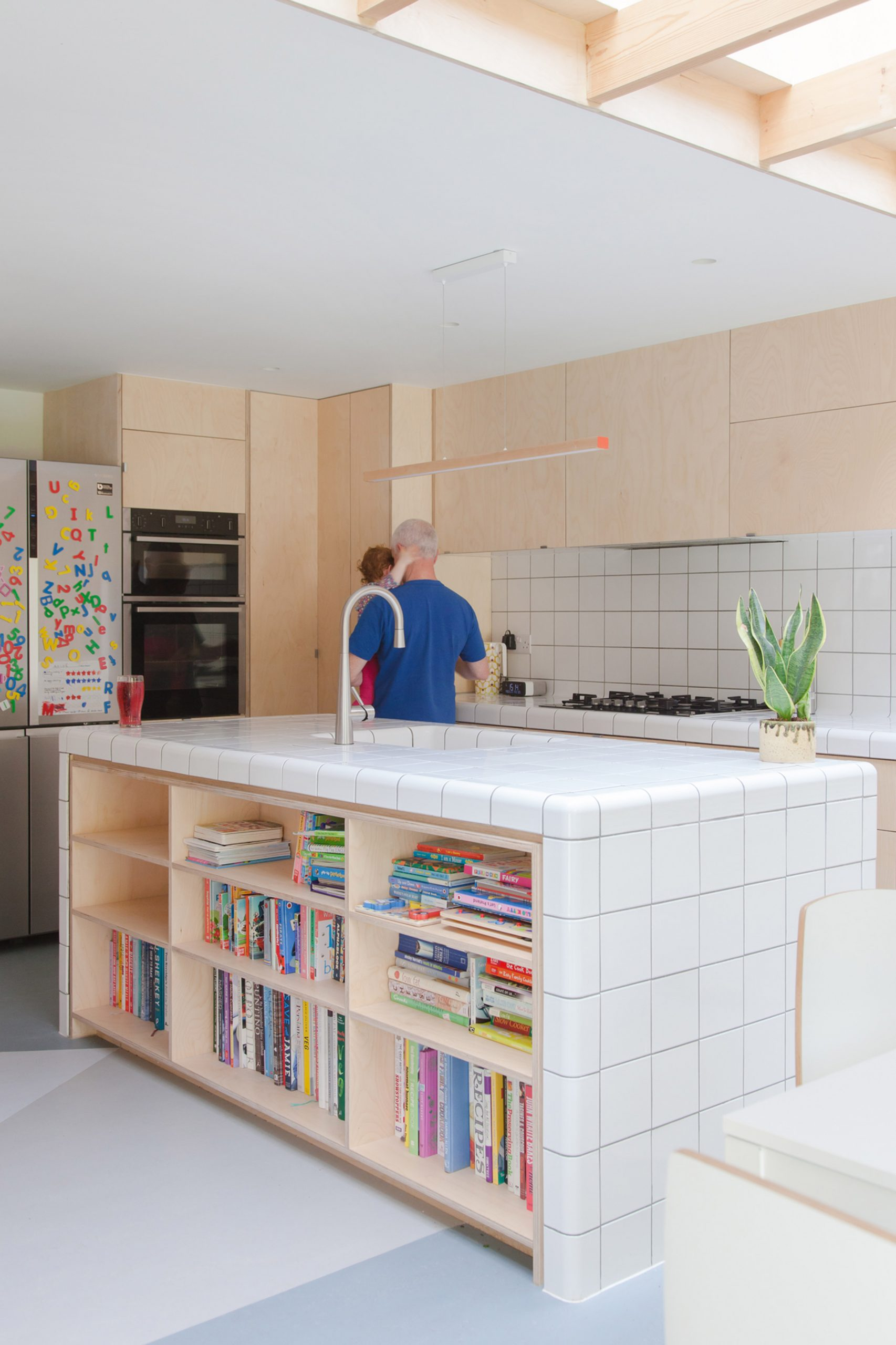A wooden kitchen with a tiled island