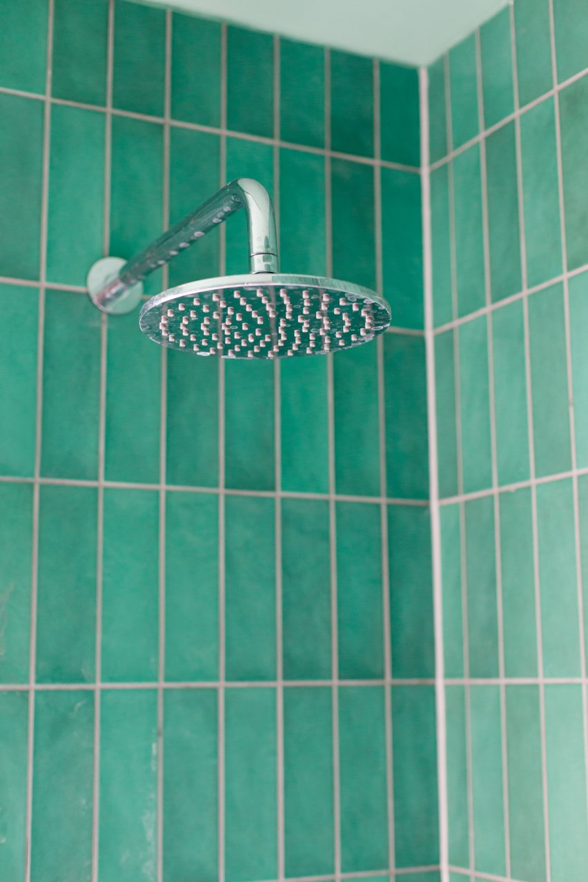A shower lined with green tiles