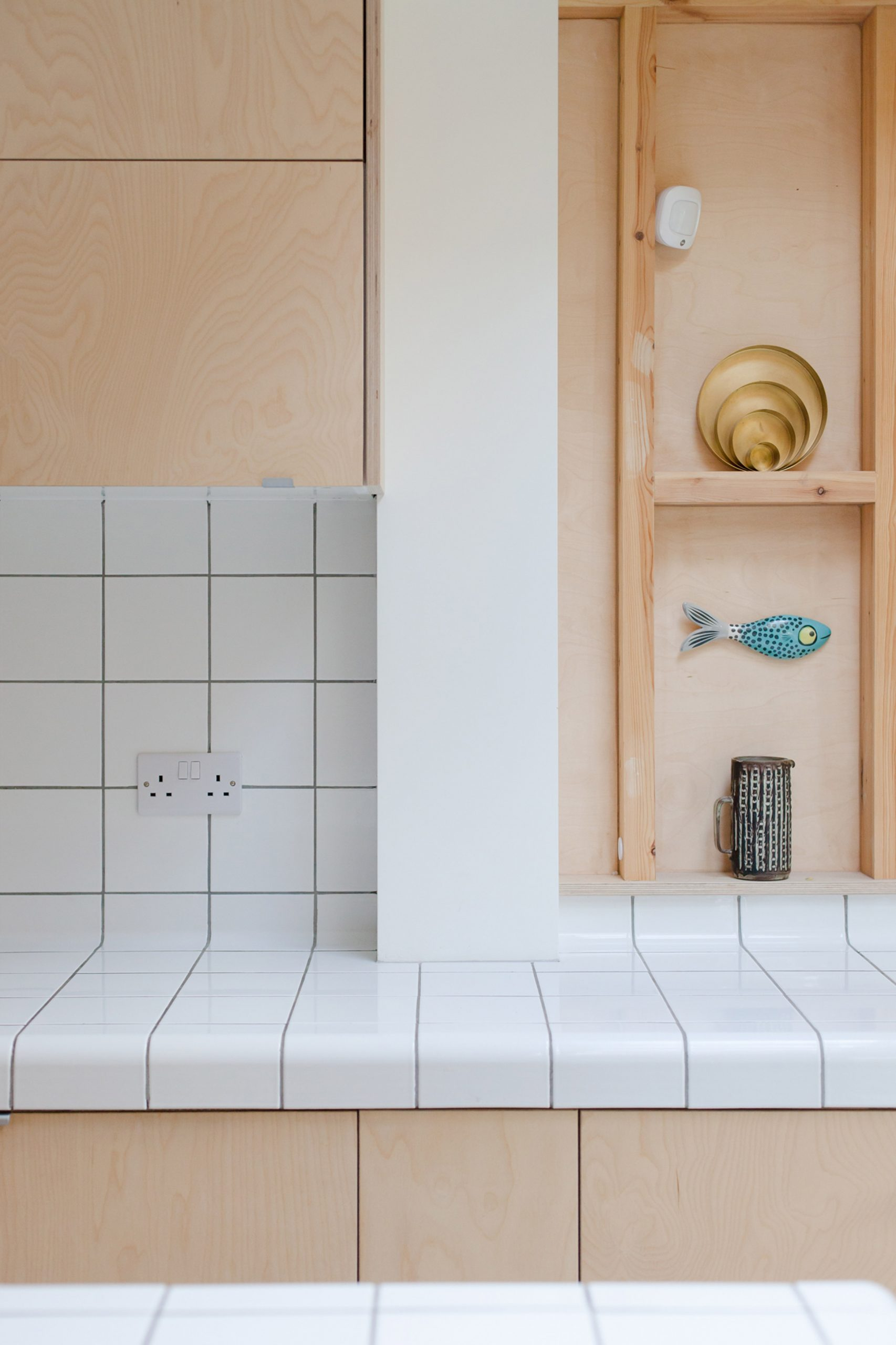 A wooden kitchen with tiled worktops