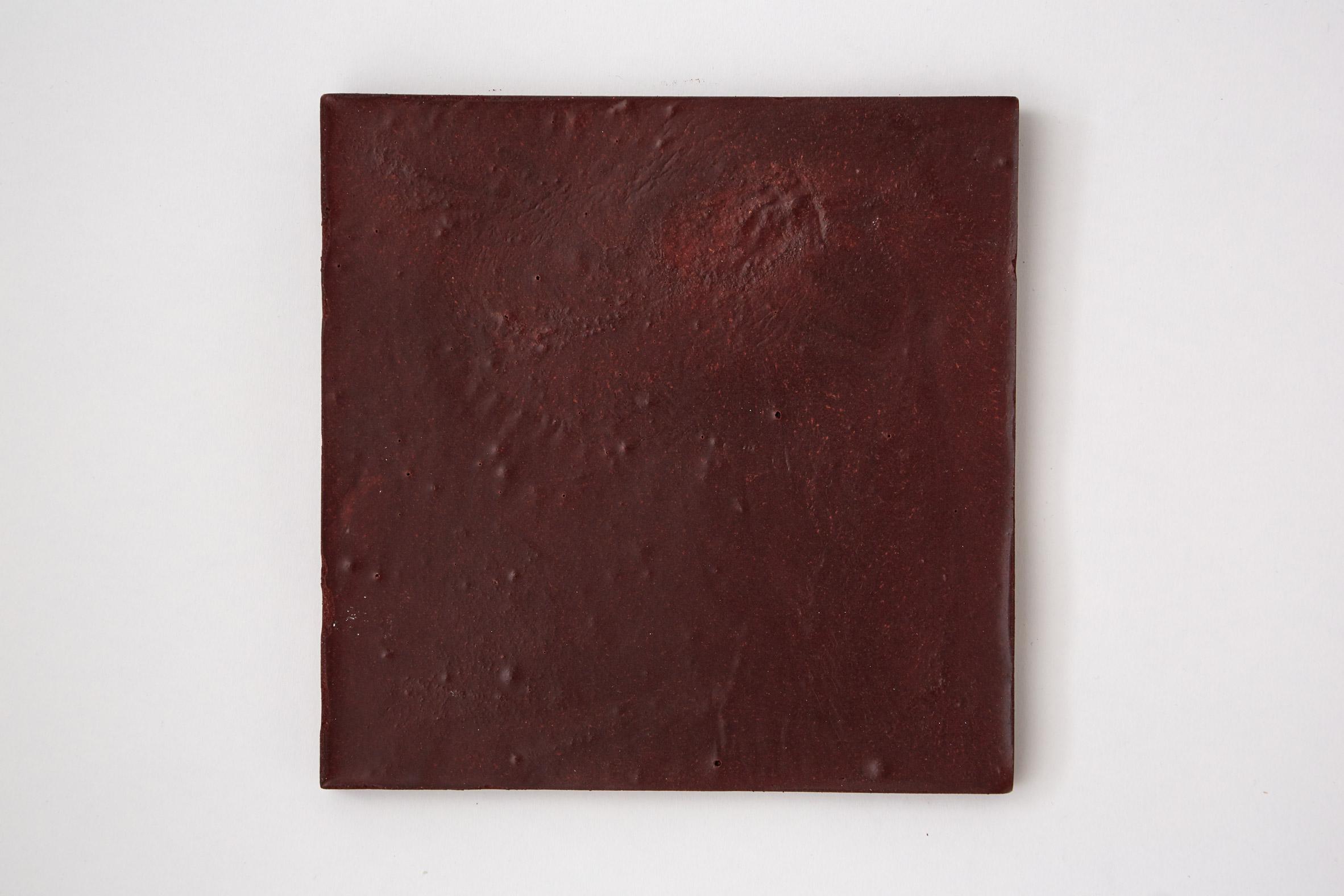 Dark red bio-concrete tile by Irene Roca Moracia and Brigitte Kock