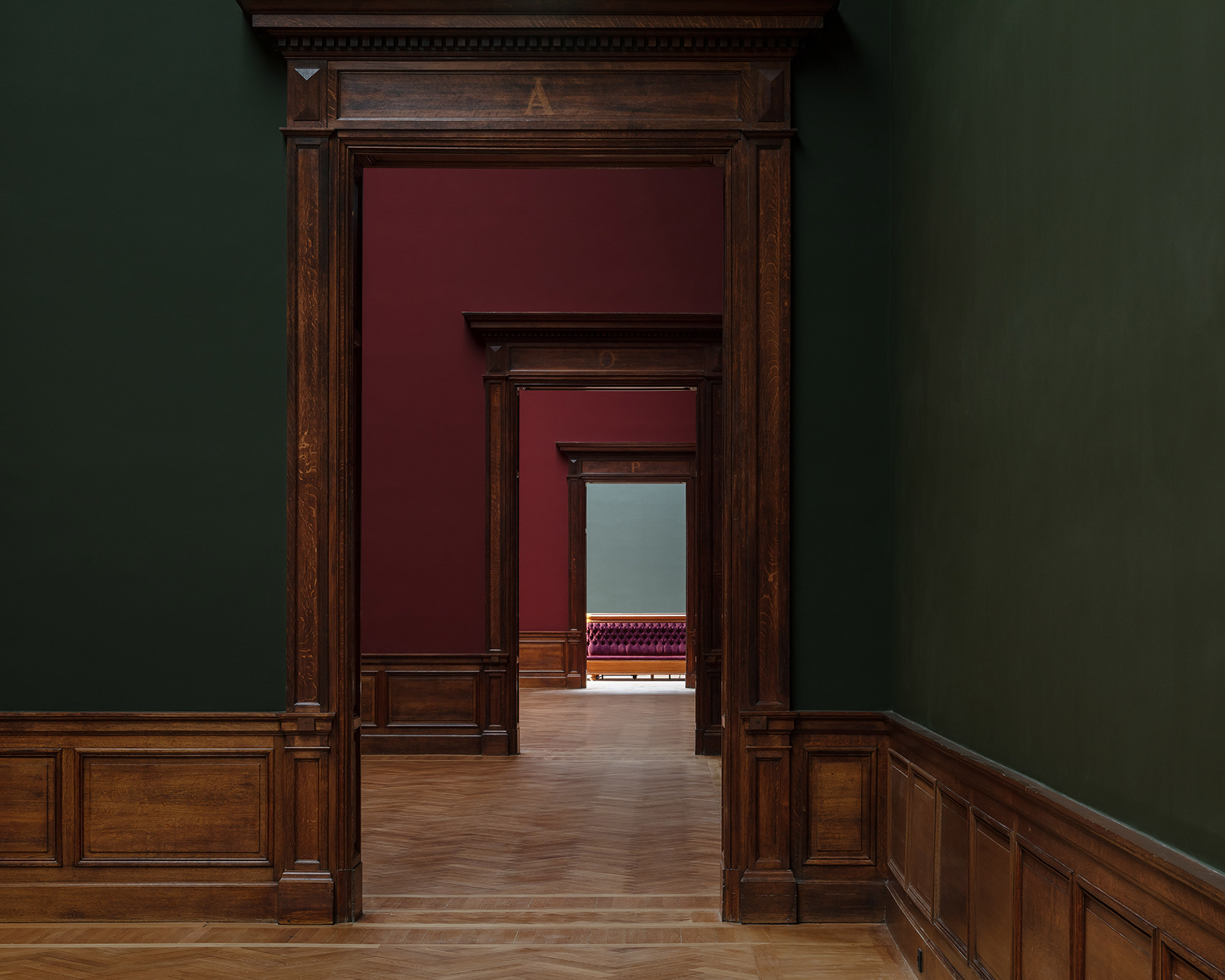 Dark green and red walls in restored 19th-century exhibition halls of Royal Museum of Fine Arts Antwerp