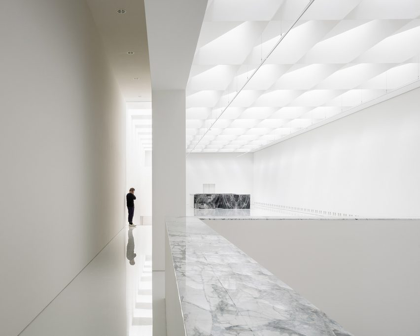 Exhibition hall in modern museum extension by Kaan Architecten with white glossy floors and marble detailing
