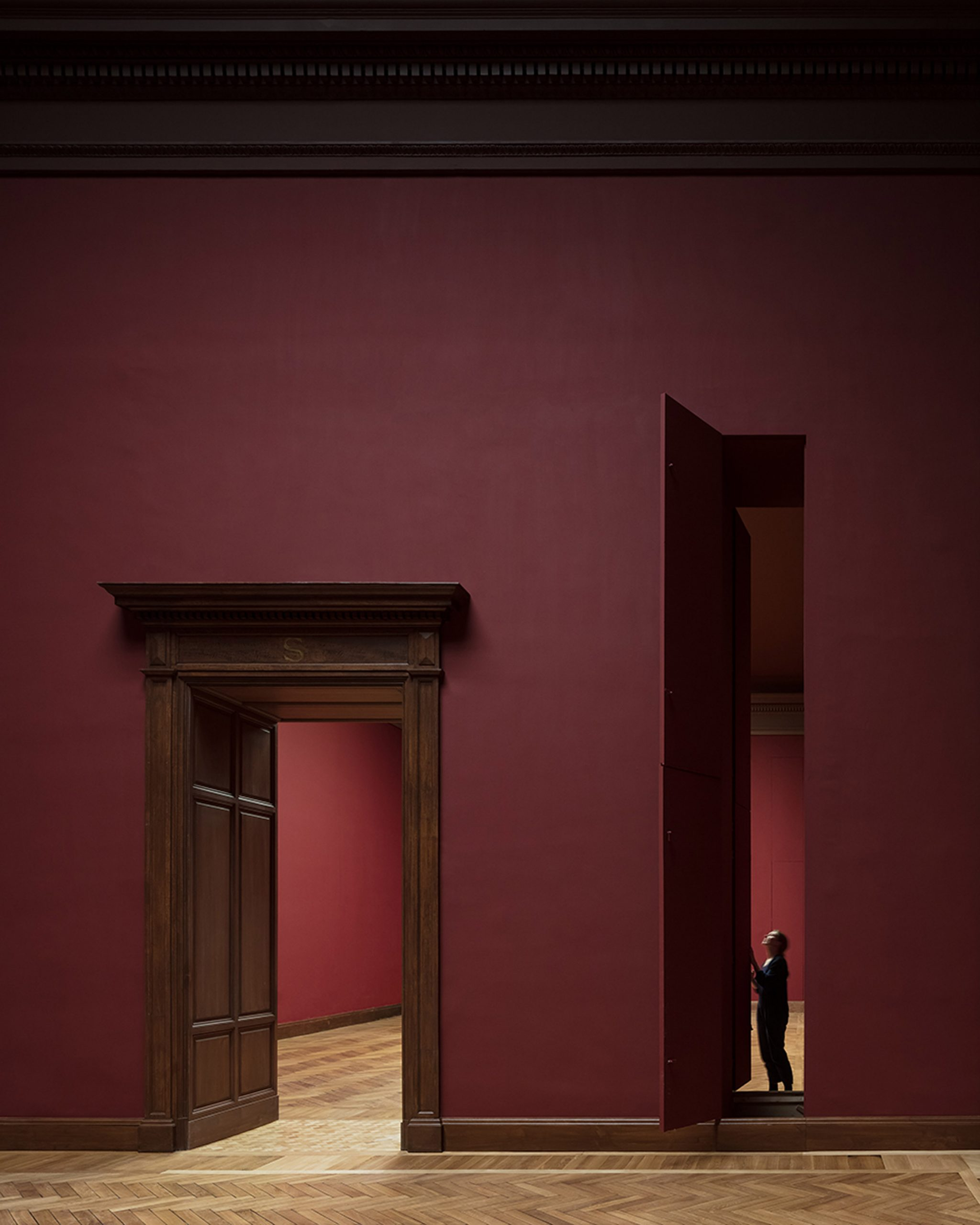 Maroon walls and vertical hatches for moving paintings in Royal Museum of Fine Arts Antwerp by Kaan Architecten