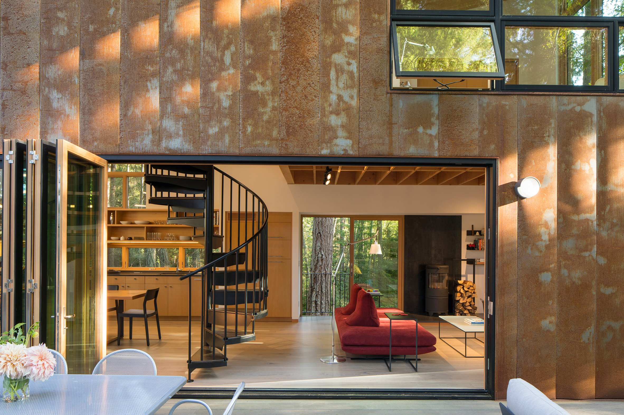 The Corten-steel house is nestled within a forest