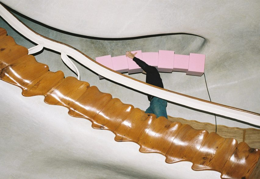 Man Enrich carries pink foam light but the stairs of Casa Batlló