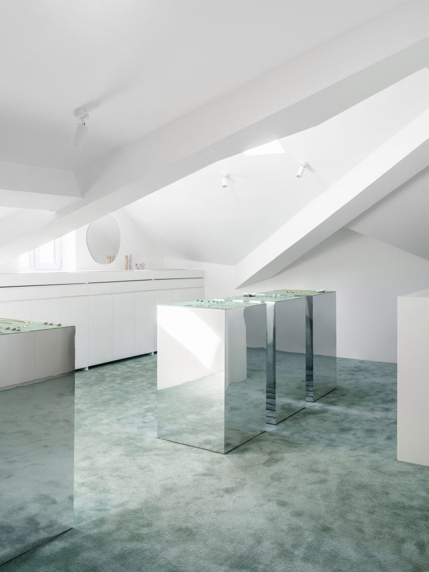 Sea-green carpet and mirrored display plinths in Qari Qris and Moonswoon showroom interior