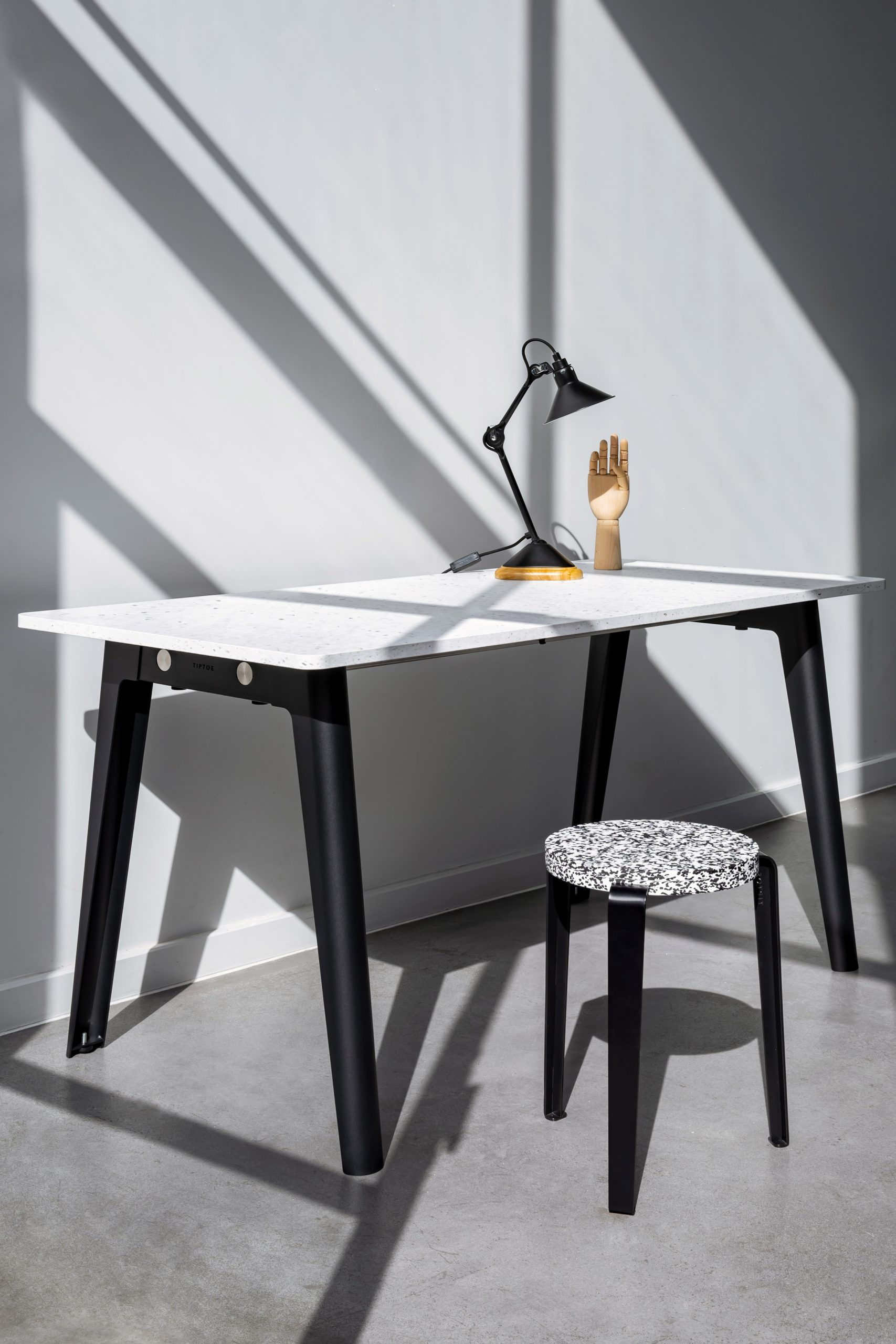 Desk by Tiptoe with black trestle-style legs and a recycled plastic top