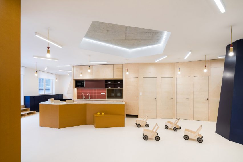 Kitchen area with plywood cladding in Prague kindergarten by No Architects