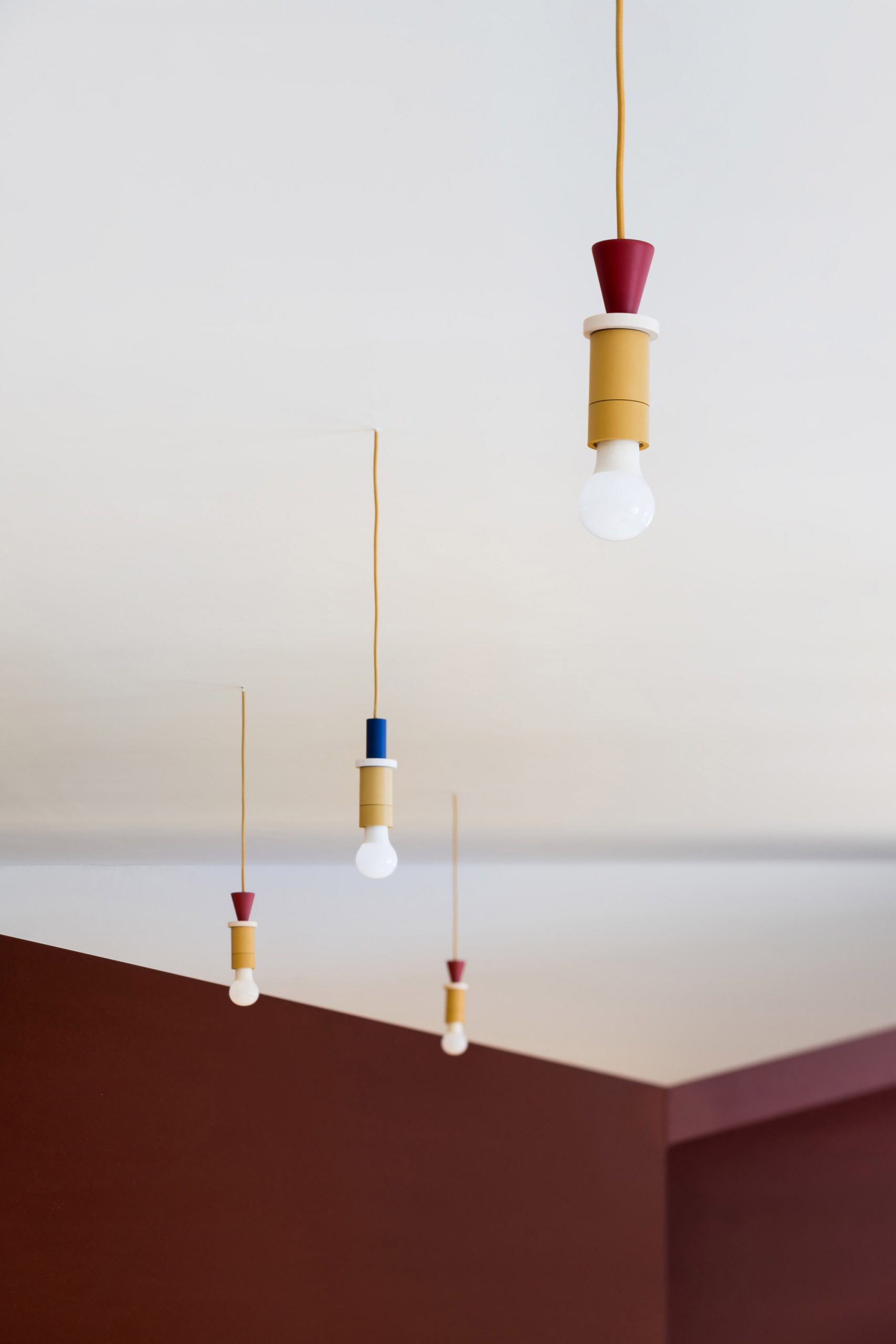 Pendant lights in mustard yellow, oxblood red and navy blue in Prague kindergarten by No Architects
