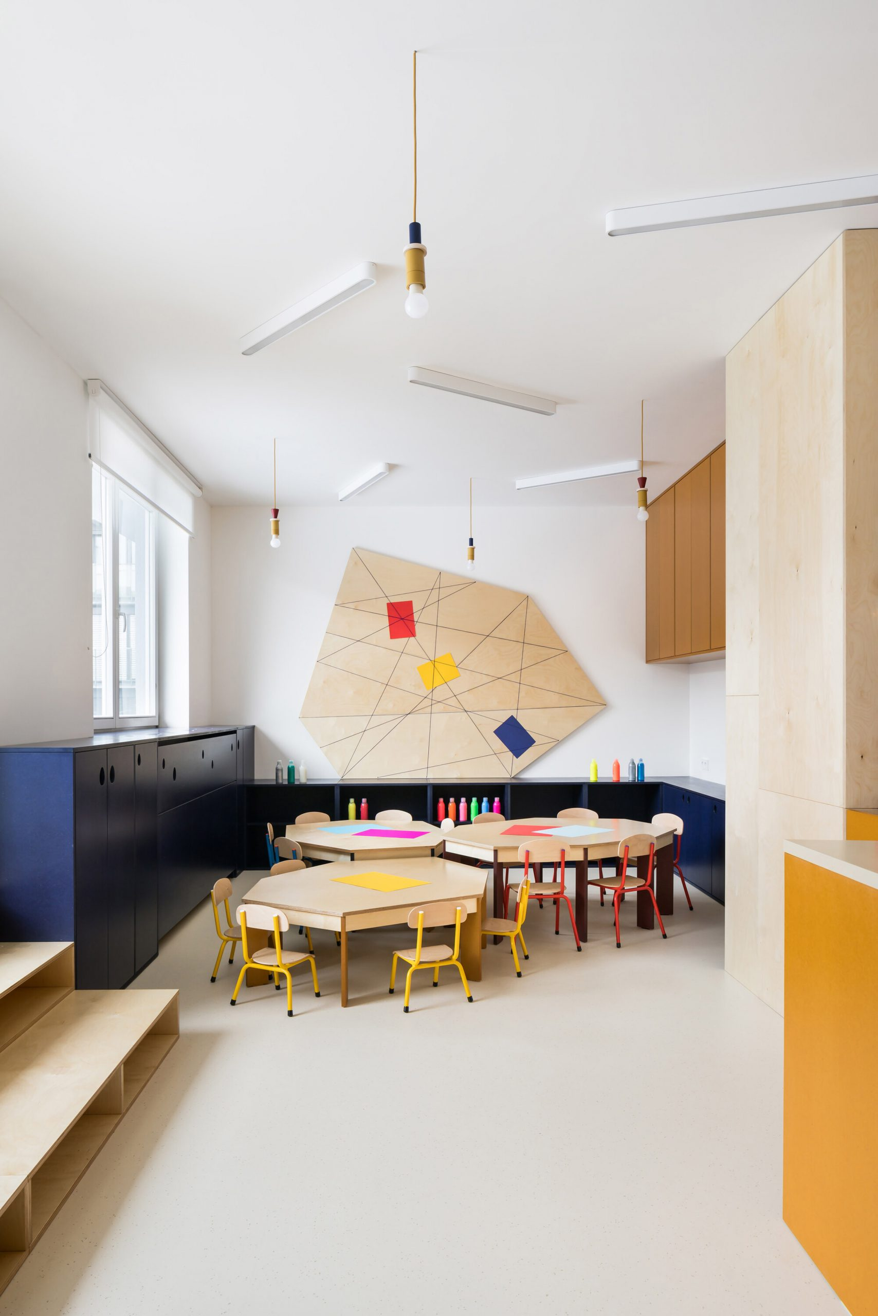 Different sized tables in drawing area of Prague kindergarten by No Architects