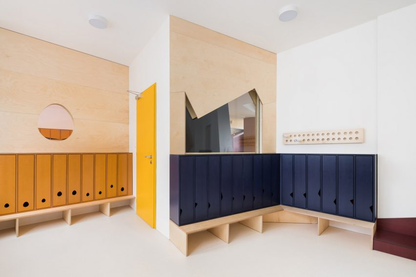 Dressing room with mustard yellow and navy blue lockers in Malvína Day Nursery