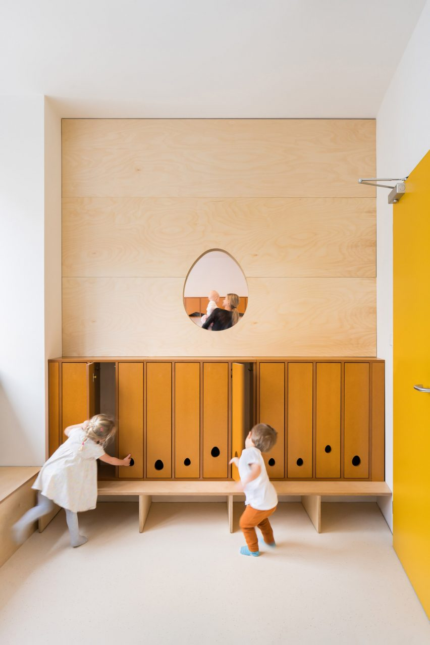 Mustard-coloured cloak room with egg-shaped window in Malvína Day Nursery