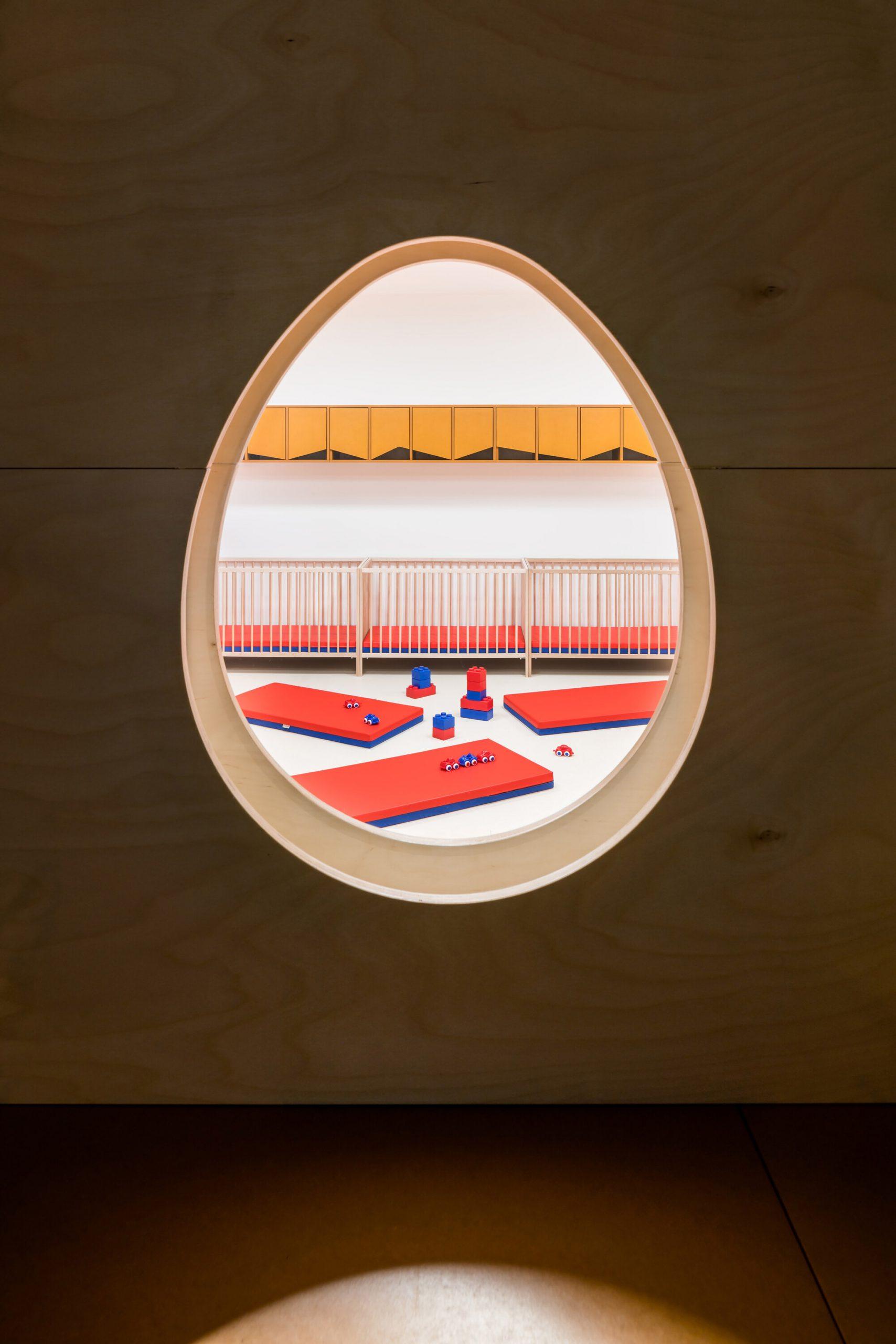 Egg-shaped window into sleeping area of Prague kindergarten by No Architects