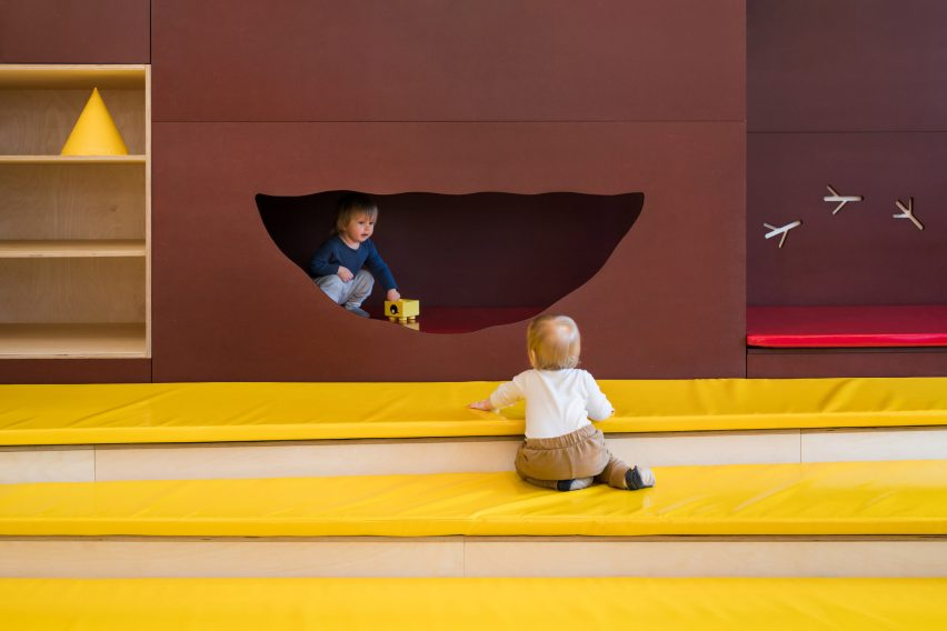 Stepped play area with yellow matts and brown nook in Prague kindergarten by No Architects
