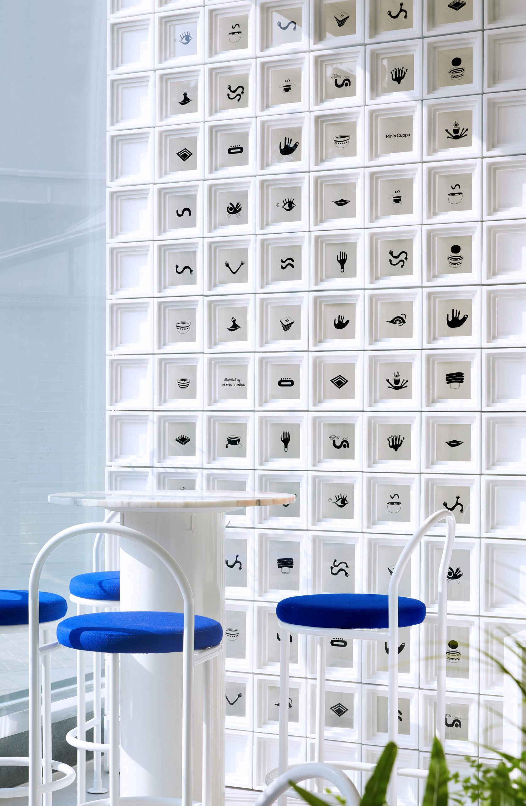 Wall of white cubes and small seating area in Shanghai's Mini Cuppa cafe