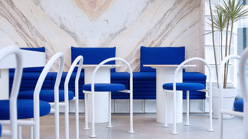 White steel furniture with indigo blue upholstery in seating area of Mini Cuppa tea shop by Raams Architecture Studio