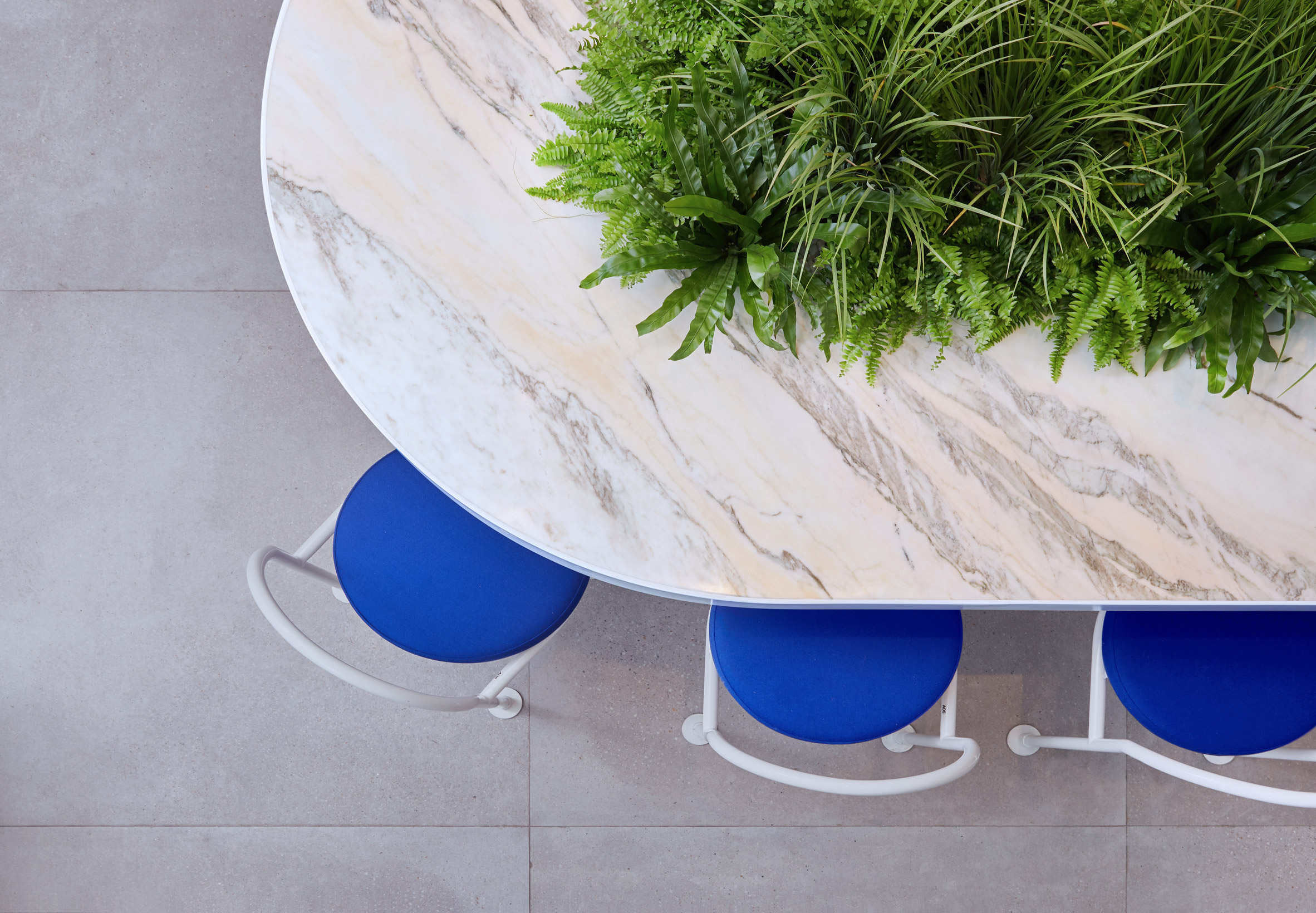 Communal marble table with central plant pot in tea shop by Raams Architecture Studio