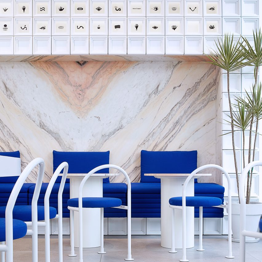 Marble panelling and white MDF blocks in seating area of Mini Cuppa tea shop by Raams Architecture Studio