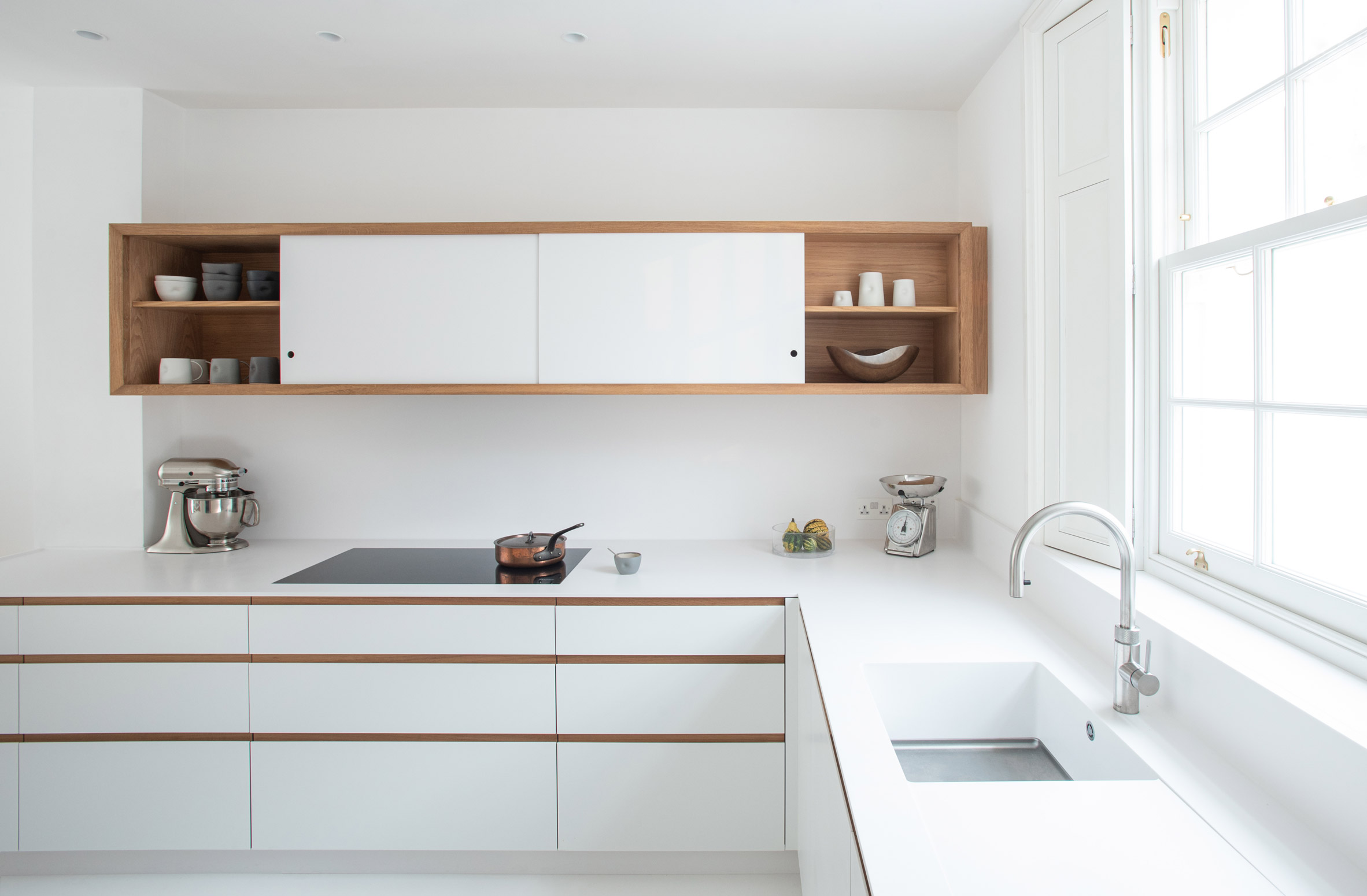 The kitchen has a white and oak palette