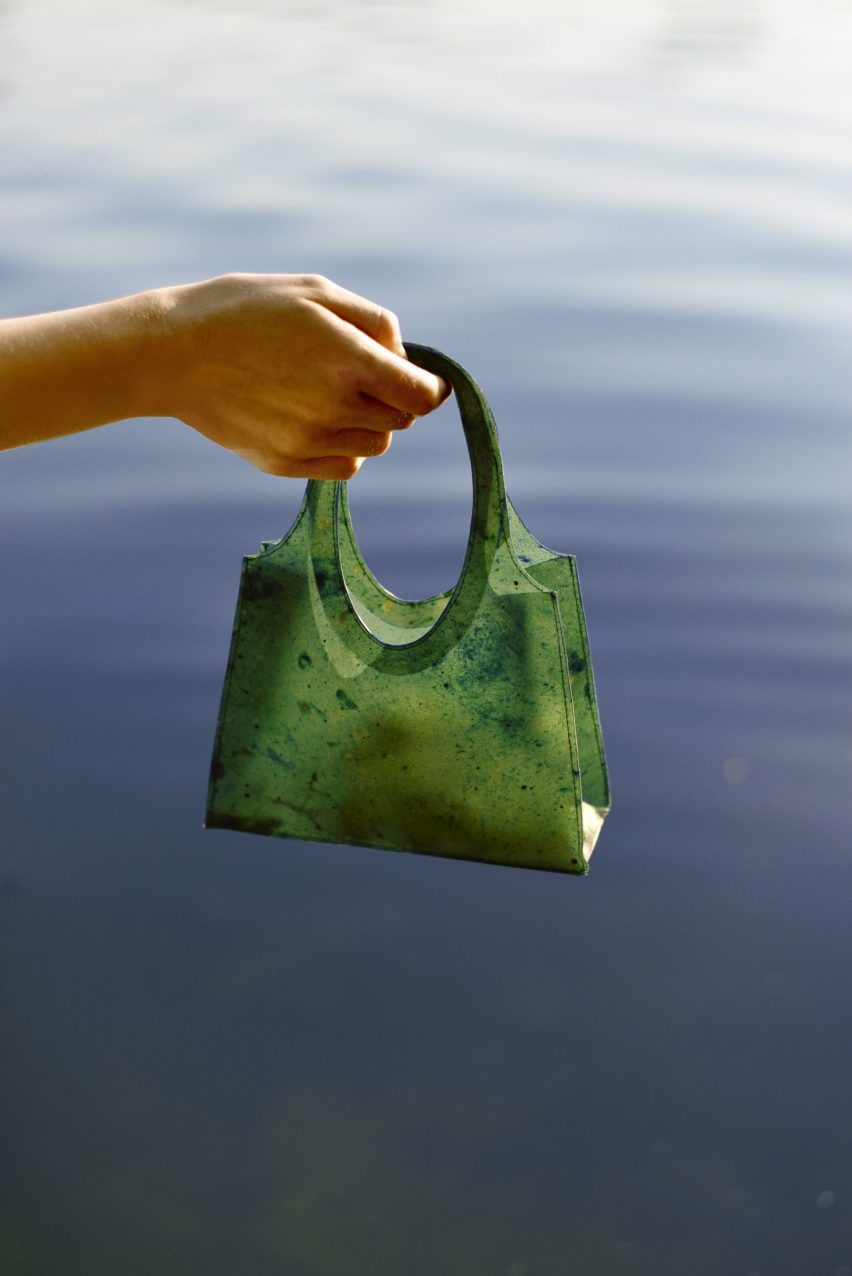 Green Sonnet155 carrier bag being dangled over water