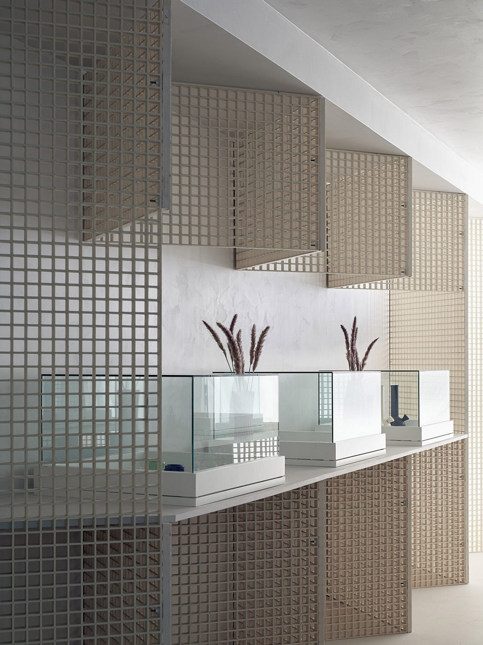 Zigzagging walls and glass display vitrines in cannabis dispensary interior by StudioAC