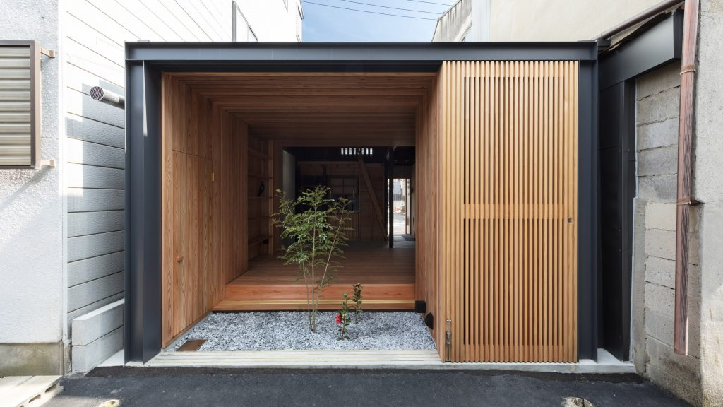 Dark roof brings loftiness to small Kyoto terrace house renovation by Atelier Luke