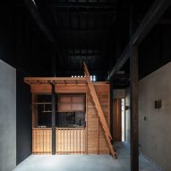 Dark roof brings loftiness to small Kyoto terrace house