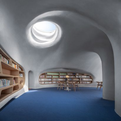 A concrete library lit by a skylight