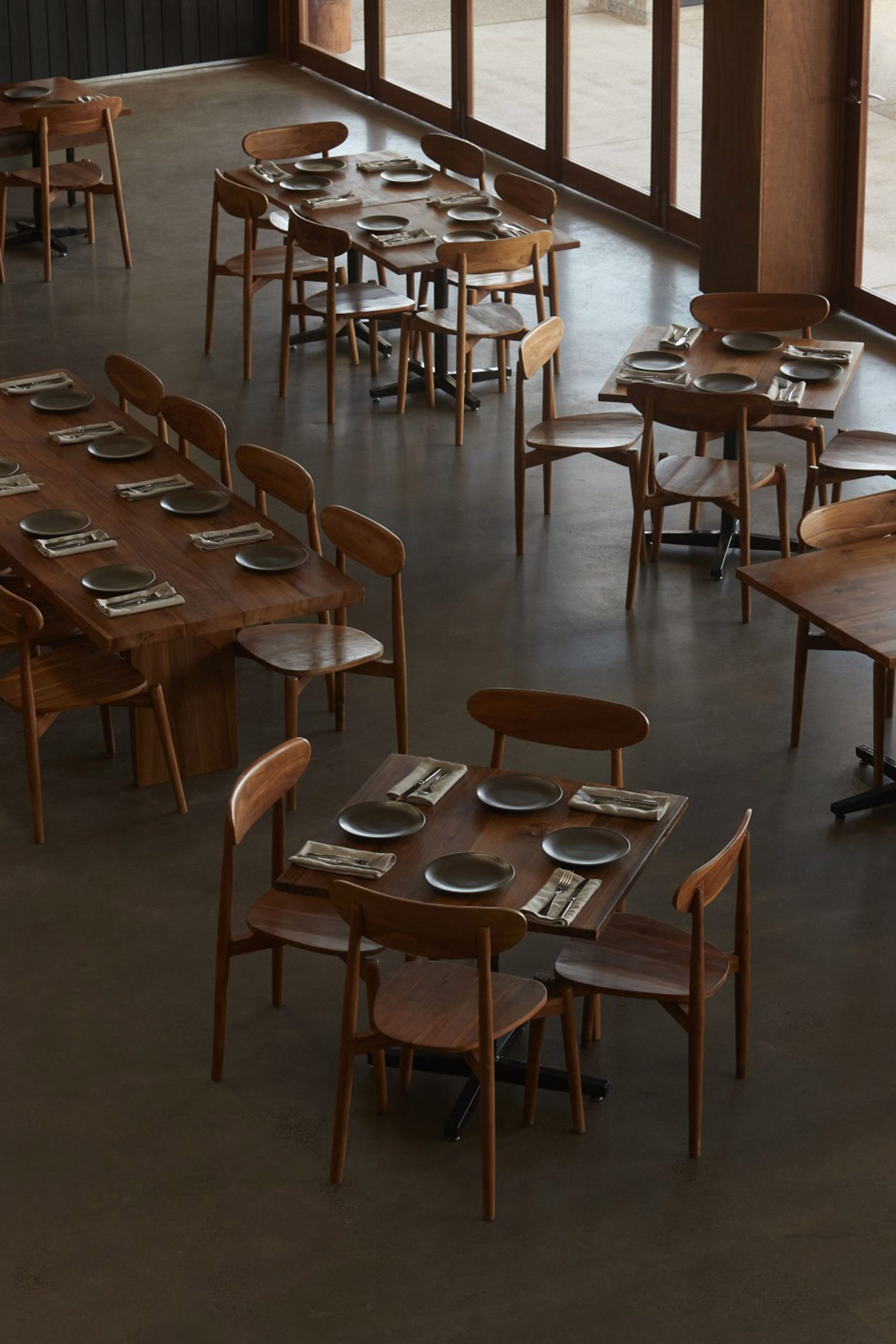 Wooden dining tables and chairs on concrete floor in Three Blue Ducks restaurant by Pattern