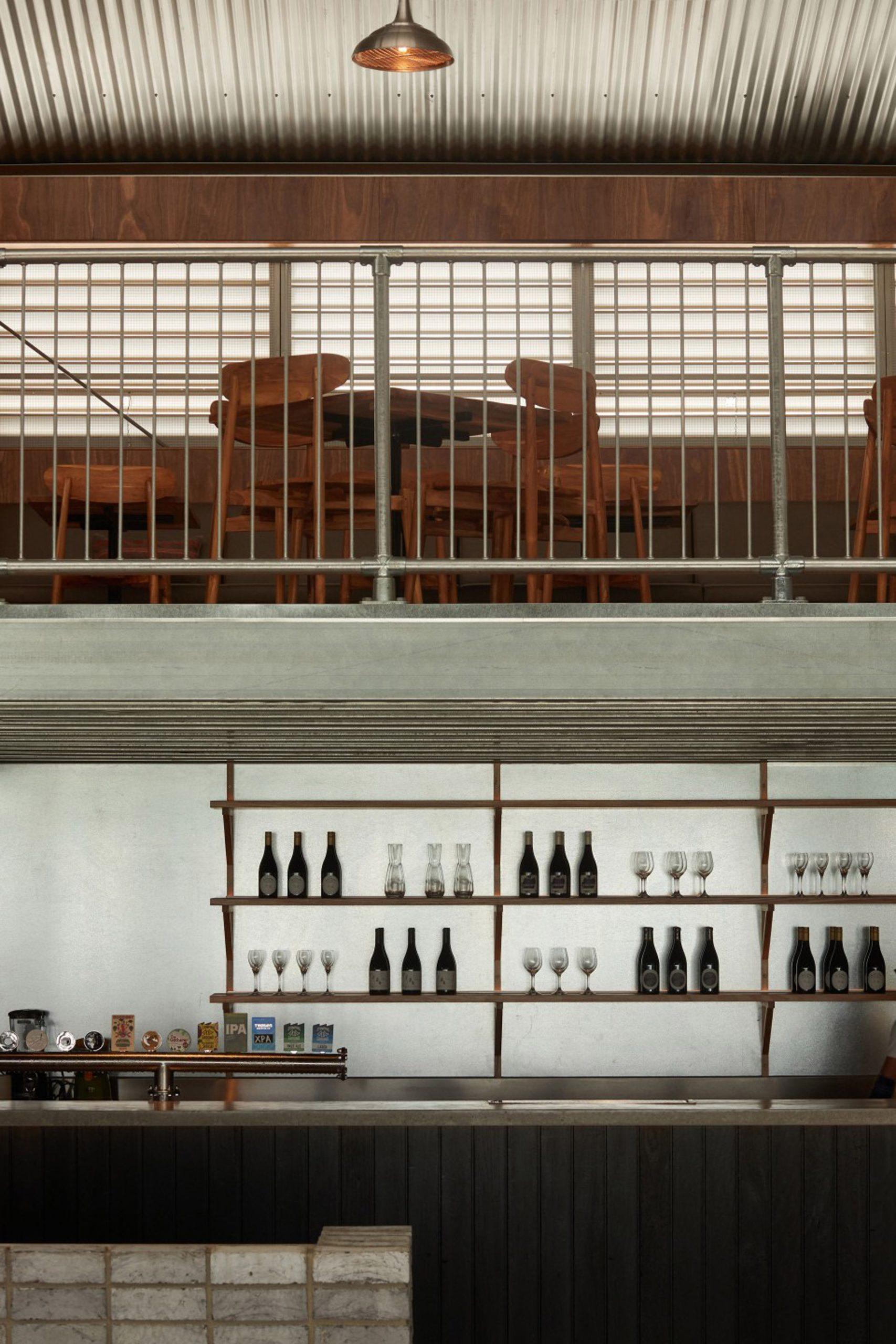 Charred wood panelled bar and steel-framed mezzanine in Melbourne Urbnsurf restaurant