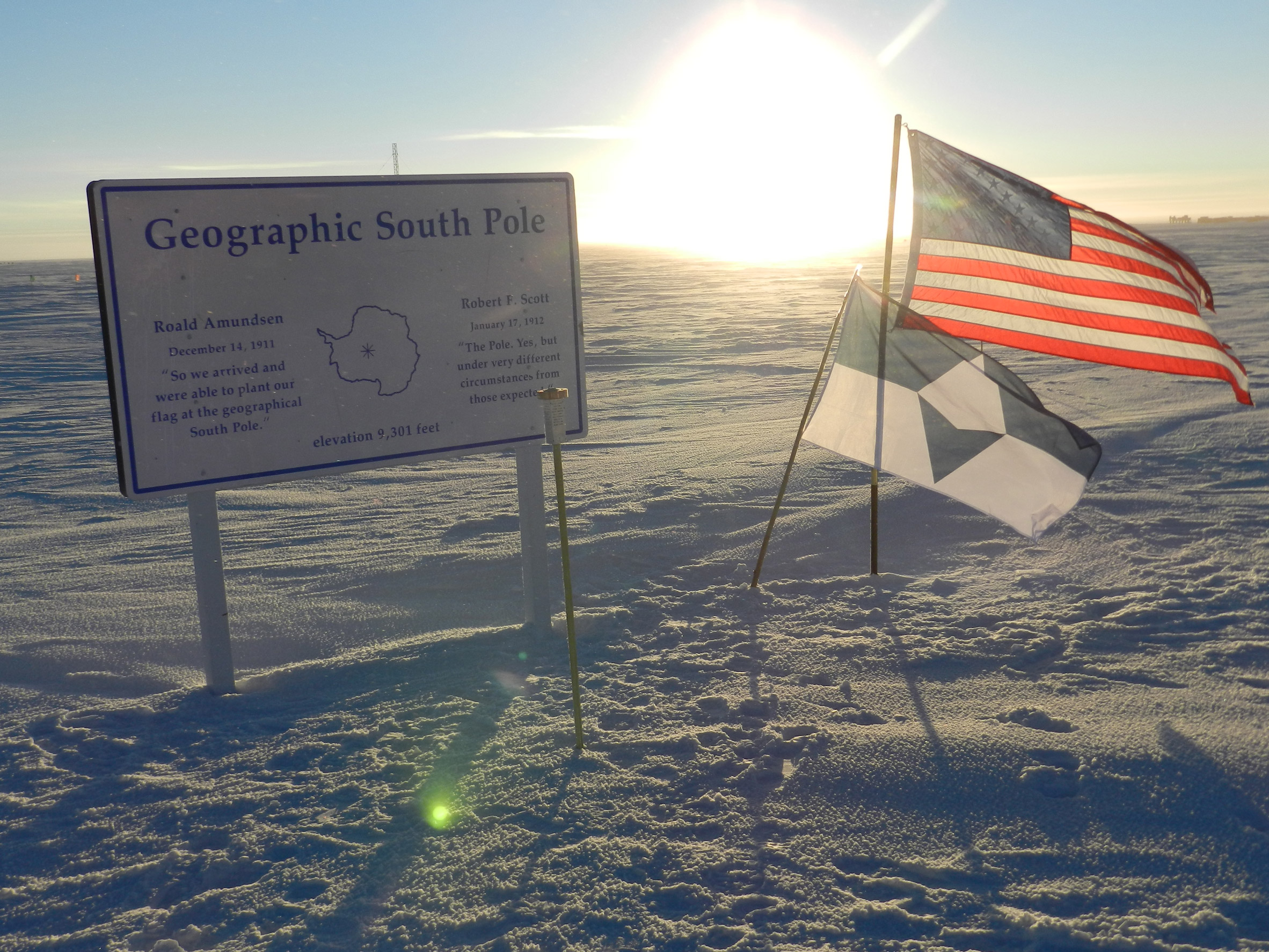 True South flag next to the US flag on the Geographic South Pole