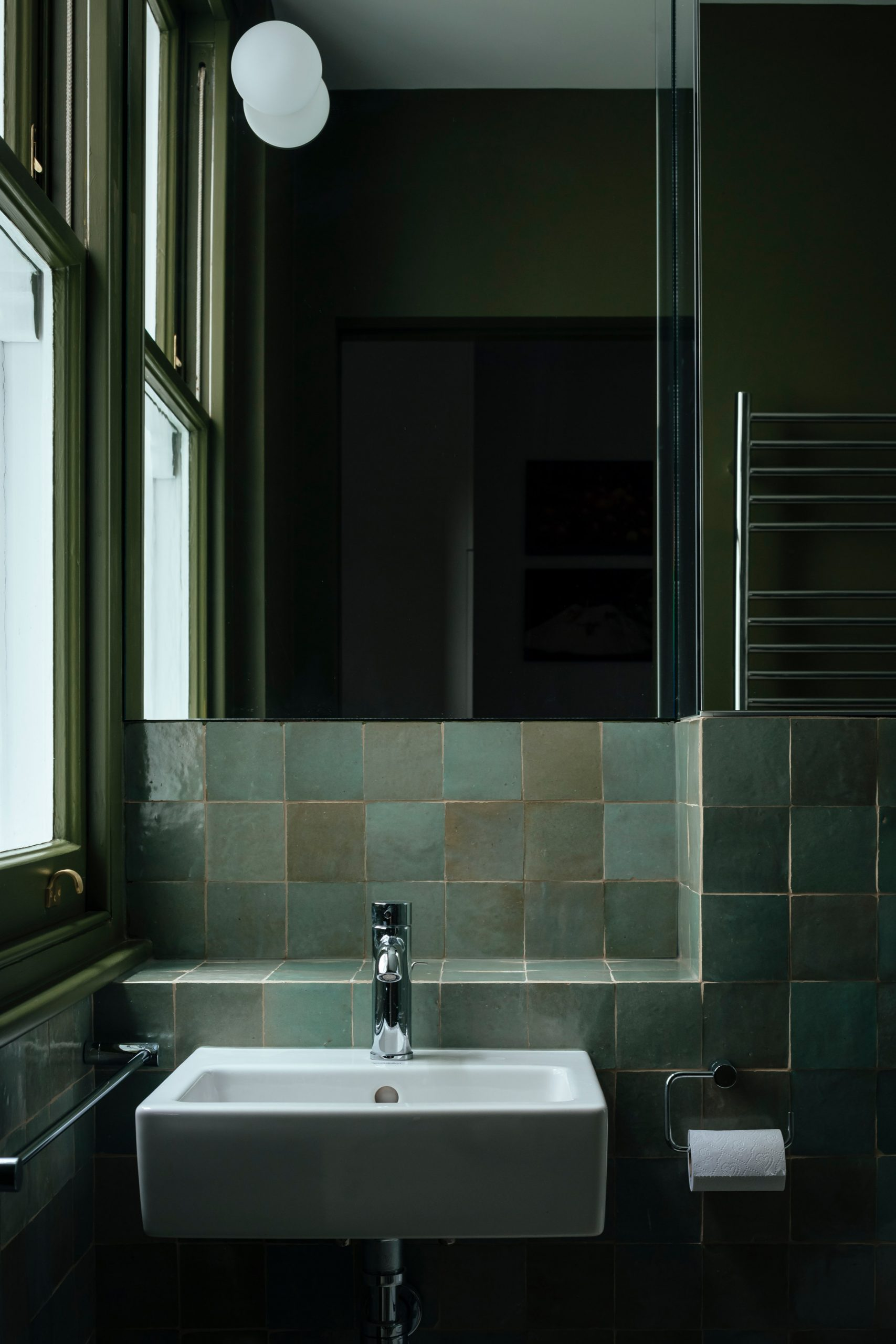 Green-tiled bathroom in Unearthed vault apartment