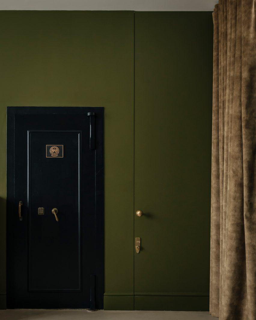 Vault door in olive green-painted guest studio of Unearthed Vault apartment
