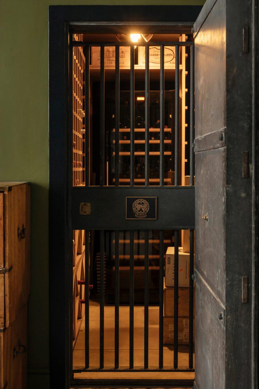 Vault door leading to wine cellar in London apartment by Daab Design