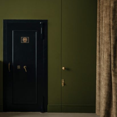Vault door of wine cellar in Unearthed Vault apartment by Daab Design