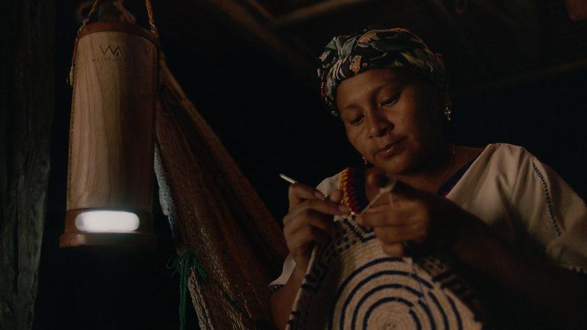 Wayúu artisan working at night using a lamp powered by salt water