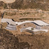 Curving stone walls allow Xerolithi vacation house to merge with Greek island landscape