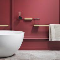Burgundy-coloured bathroom with brushed gold towel rails