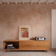 Timber console with art objects against a blush pink wall