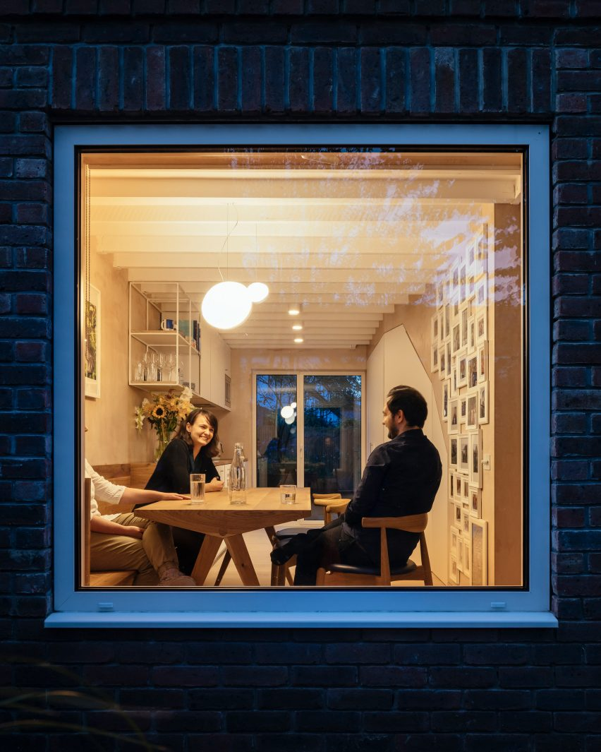 Large square window looking into house with people dining