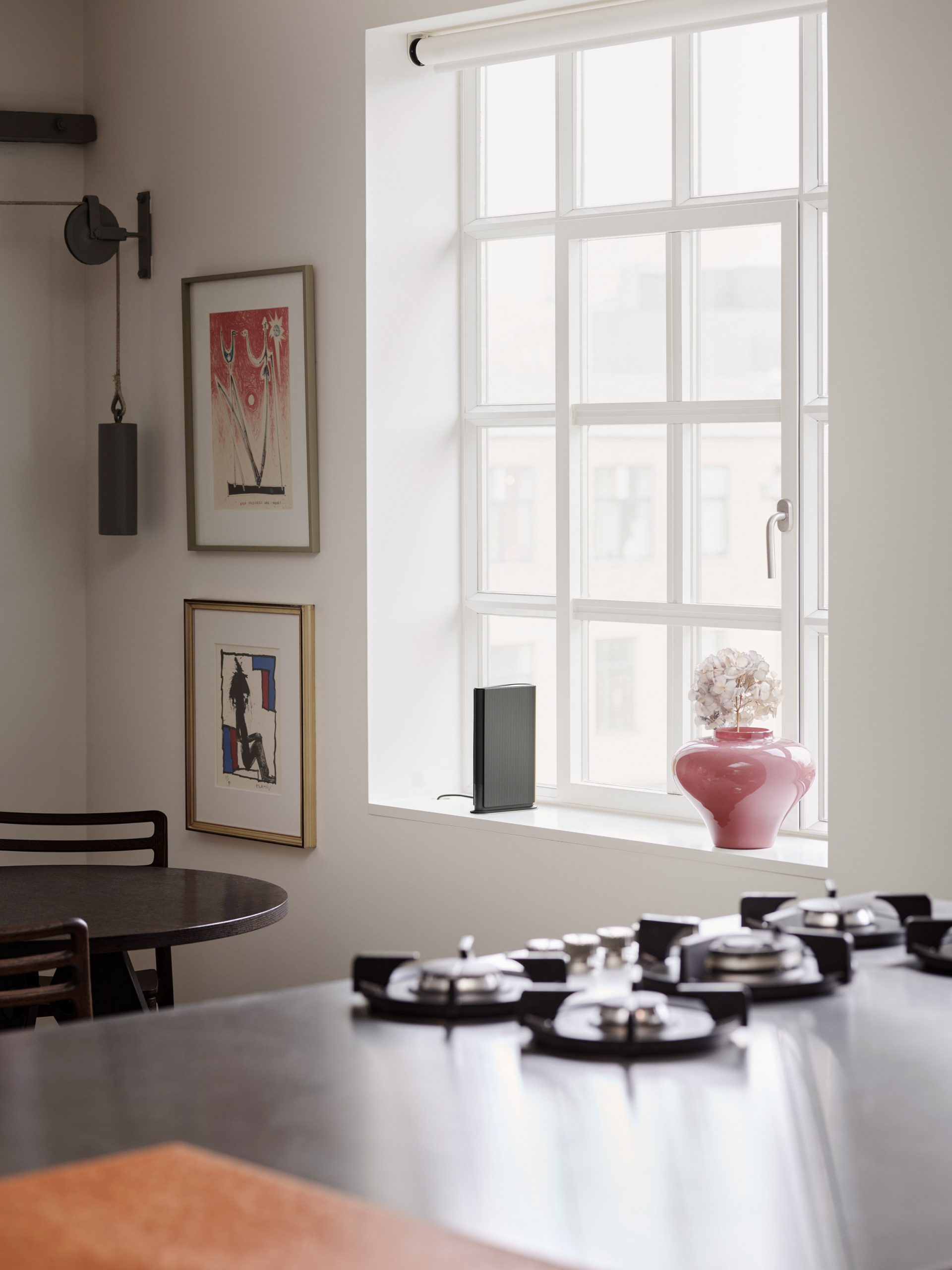 The Beosound Emerge sits on the ledge of a kitchen window